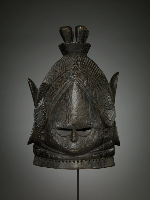 very small, teardrop-shaped face; small smiling mouth; narrow eyes with half-circles beneath them; small nose; C-shaped ears; elaborate hat or hairstyle with top element with four vertical protrusions; strap-like element around back and sides of head hold down four vertical elements; hair/hat decorated overall with incised designs of radiating arcs, grids; lines, radiating squares and triangular shapes; dark brown patina