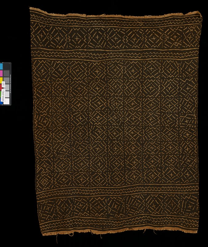 light and dark brown textile with geometric designs; constructed from nine strips stitched together; geometric designs include crosses, zig zags, and arrows; shorter edges of textile have fringe