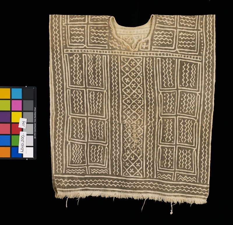 black and white textile decorated with geometric patterns including zig zags, creases, and diamonds; large pocket located at center of torso; shirt is completely open at sides; fringe along bottom edge