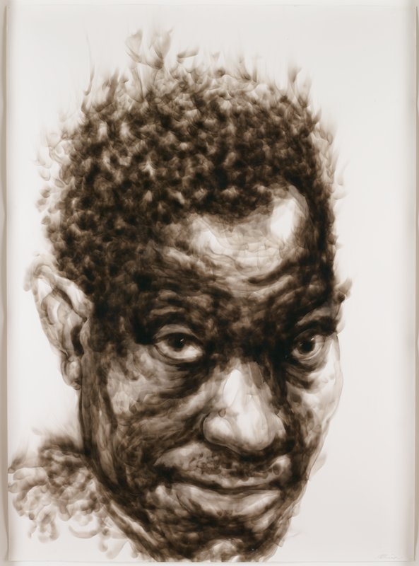 portrait of a dark skinned man with short hair, sticking up on top of his head