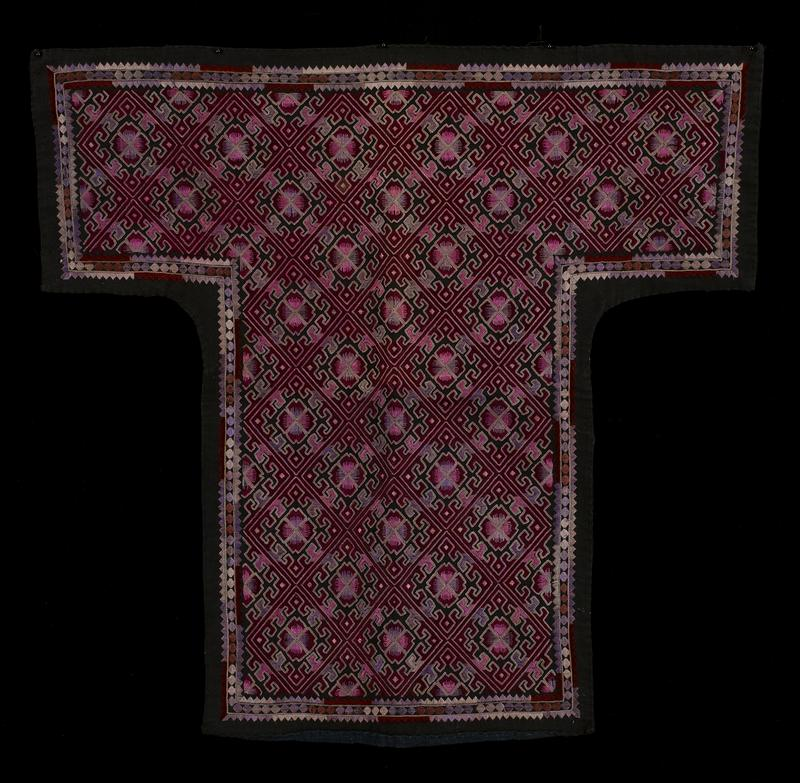 "predominantly black with multicolored geometric embroidery; embroidered pattern predominantly consists of dark pink color; baby carrier is in the shape of a capital ""T""; back of carrier consists of blue and black cloth"