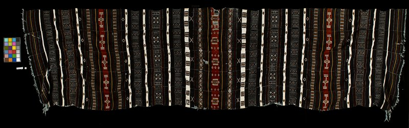"predominantly black textile with multicolored geometric designs; geometric figures include diamonds, triangles, and ""x""s; textile constructed of six long strips; geometric patterns are white, brown, and tan in color"