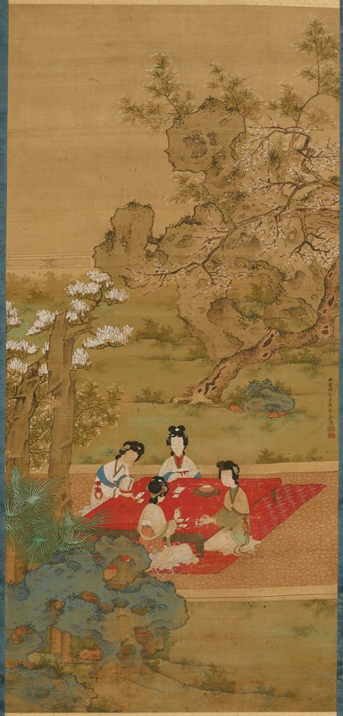 four ladies seated around a low red table on a red flowered carpet on a stone pathway in a garden, playing a game with cards or tiles; trees with white blossoms behind path at center and in front of path at left; blue rocks, LRC; grey rock, URQ