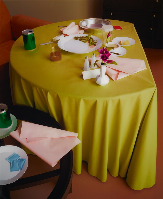 "photographic image of paper construction of dirty dishes, glasses, beverage cans, salt and pepper shakers, flowers in a vase, napkins, etc., after a meal, on a small table with a green ""tablecloth""; image face mounted to Plexi with aluminum backing; aluminum ""frame"" on back"