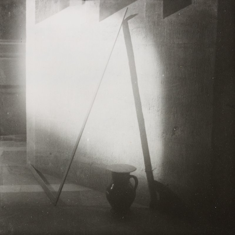 handled jug on floor with cover at center; L-shaped element leaning against wall casting shadow forming triangular shape at center; door at left in ULC
