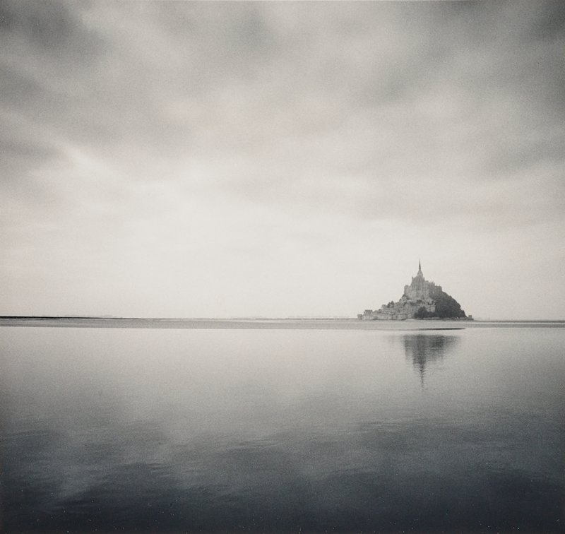 island with buildings and spire at right on horizon line; calm water