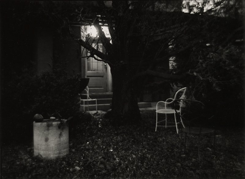 bare tree at center; leaves on ground; three metal chairs in yard under tree; door with light behind tree
