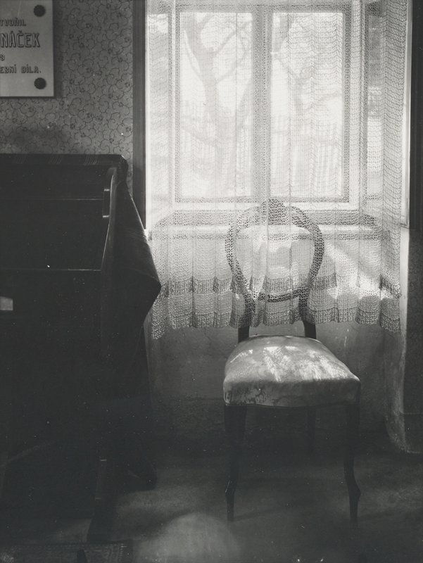 side chair with a lacey semi-transparent curtain falling over the backrest; trees and fence visible through window above chair