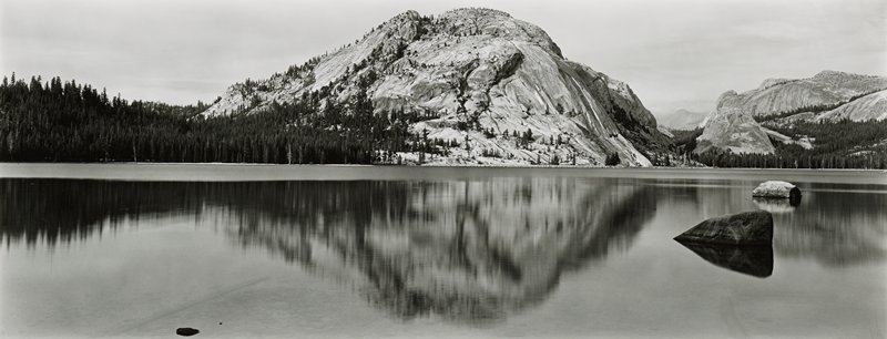 water in foreground with reflection of rugged mountain peak at middle background; pine trees at left in background