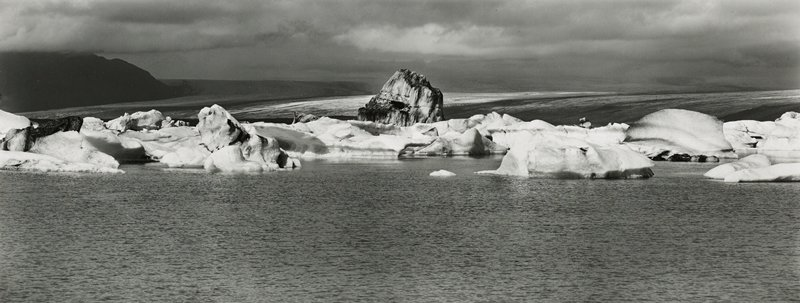 slightly dirty snow/ice mounds in water, with large dirty snow/ice mound at center; water in foreground with small waves; flat land in background, with black hill at left
