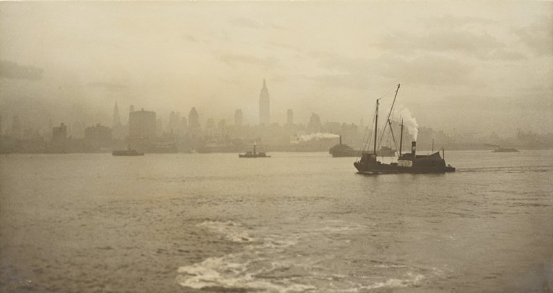 boats in middle ground; view of New York skyline in background beyond water
