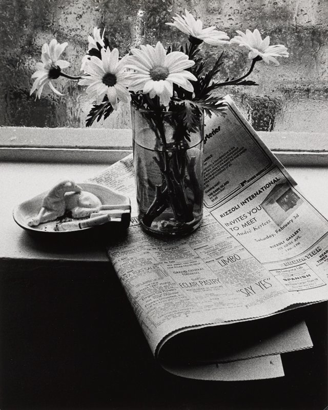 "ashtray with a figure of a dog and a glass with daisies on a windowsill, resting on a folded newspaper with an ad in the corner: ""RIZZOLI INTERNATIONAL INVITES YOU TO MEET André Kertesz""; rain outside window"