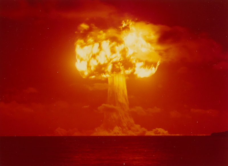fiery atomic bomb mushroom cloud; orange sky; flaming cloud over water
