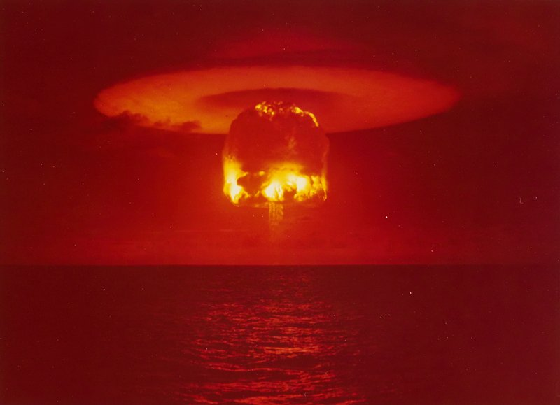 fiery atomic bomb mushroom cloud; dark orange sky; flying saucer-shaped cloud in sky with fiery round cloud underneath it, over water