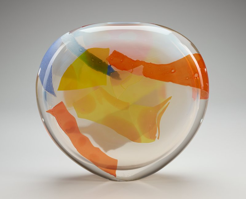 flattened disk-shaped vessel with very small foot; orange, blue, yellow and white irregularly-shaped elements layered on surface; clear/white glass