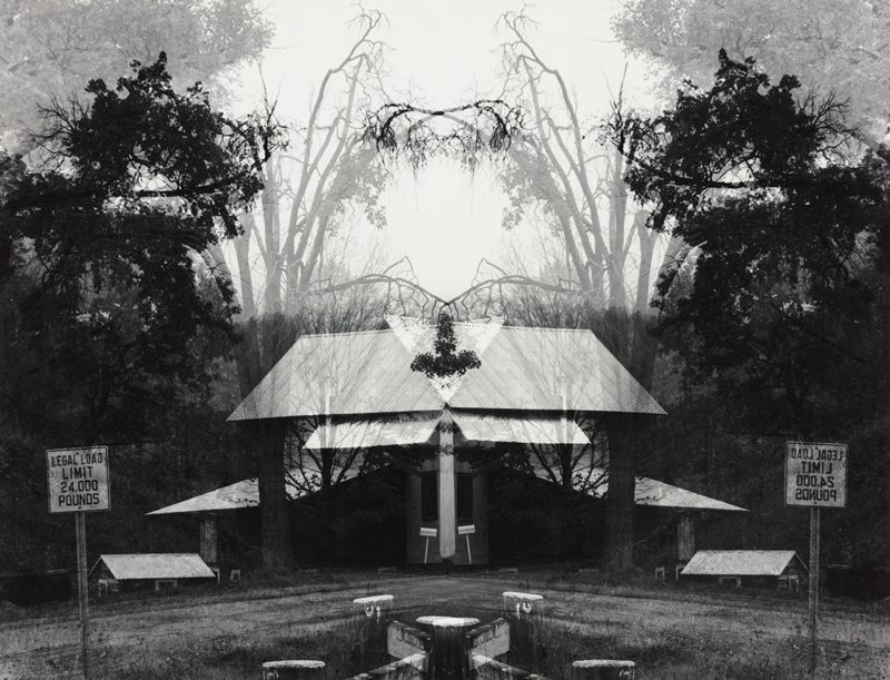 two negatives, in reverse, forming a symmetrical image; building at center; signs at left and right; trees