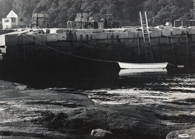 boat at right, tethered to block wall with a long rope; house, ULC; crab fishing traps stacked beyond block wall at water's edge; ladder down to water, ULQ