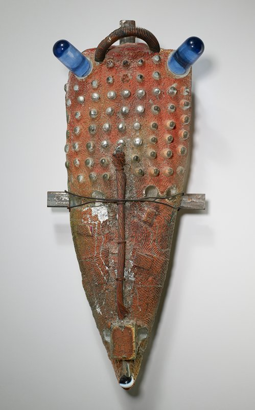 mask; roughly triangular boat-like form; pebbled surface with rust-colored surface accretions; protruding elements in rows on forehead; rounded, blue glass horns; rounded, handle-like, C-shaped fluted metal element at top center; vertical bundle of copper wires through center; dark blue and white glass piece at bottom; attached to cross-shaped metal hanger with adhesive and horizontal loops of wire across center
