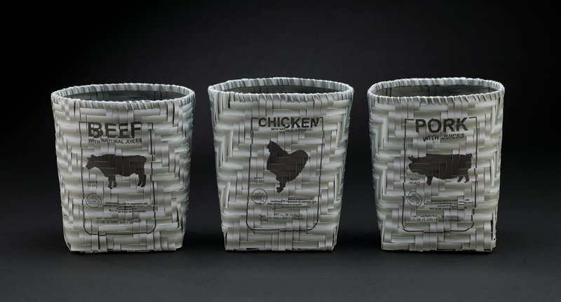 "woven basket with square bottom made of strips of grey paper; strips printed on front of basket with a label reading ""CHICKEN WITH NATURAL JUICES"" and other text and silhouette of a chicken"