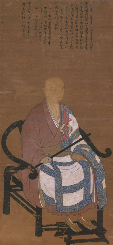 man sitting on black chair holding black rod; wearing brown robe with white and blue on lap and PL arm