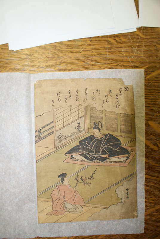 two men seated in tatami room; older man, wide stance, wearing large black robe and tall headdress sits on a carpet; in front, a younger man with pink robe kneels, offering a plum branch with a bird; clouds at top and LR with inscription