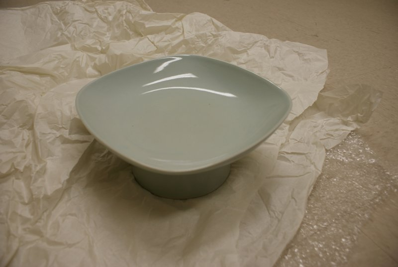 square celadon dish with rounded edges on attached circular pedestal with flared base