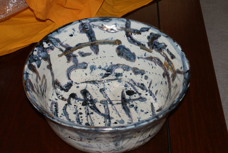 large bowl with deep walls; purple, blue, and gold abstract designs on white background; gold painted rim; a few deeper impressions with gold pigment inside