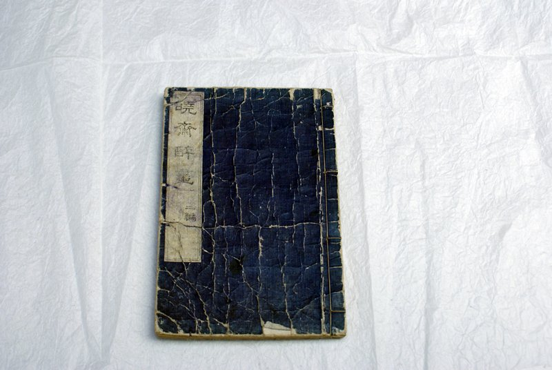 string bound book with dark blue cover; woodblock images of humans, animals, and demons engaging in humorous, dramatic activities