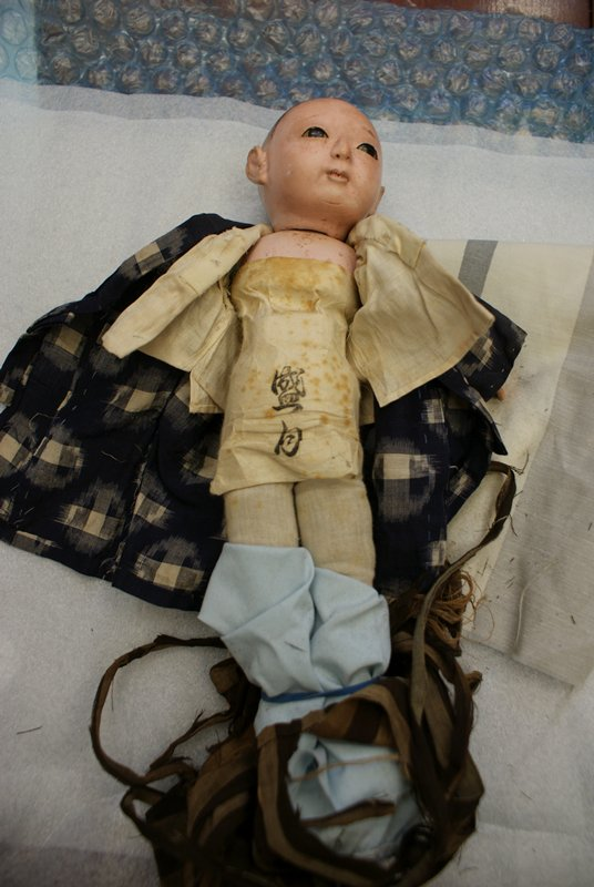 little boy doll with painted hair, inlaid eyes; painted pink skin; dressed in blue and white kimono with brown striped hakama; head swivels at neck