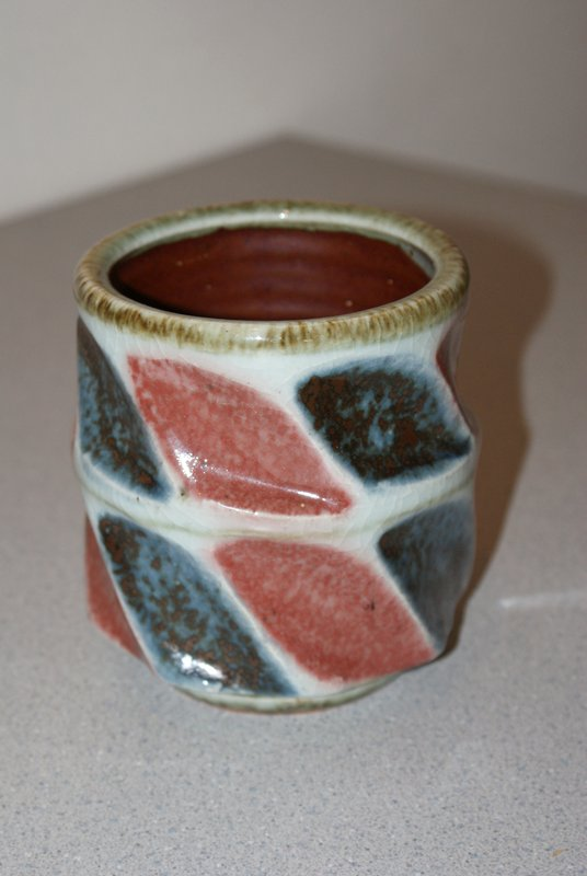 pot with wide, deep diagonal indentations alternating between blue and brick red; green lip and base; thin green line around center; dark red with opalescent glaze inside