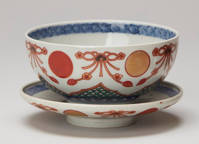 rounded bowl with ring foot; exterior decorated with alternating circles of gold and red flanked by gold floral garlands; triangular band with green loops around foot; blue and white spiral and floral bands at interior; character in gold bordered with red at interior; saucer-shaped cover has similar decorations as bowl; four characters in blue on underside