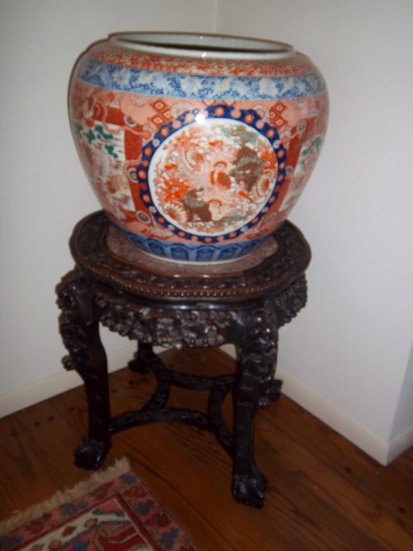 large porcelain vase with Chinese style imagery; alternating vignettes of golden lions inside a decorative blue circular border, and a group of scholars within a red square border with a phoenix at top; red and blue bands with flowers around top