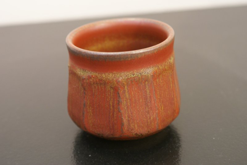red sake cup with wide vertical ridges starting below lip; some ochre and black accents; gray highlights around lip; ochre and black inside