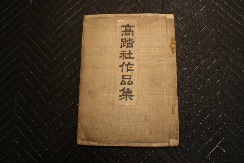 heavily worn ribbon bound book with black and white copied images of birds, flowers, insects, and decorative designs and motifs