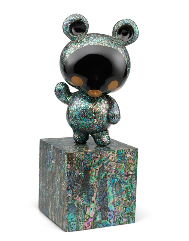 small panda figure with PR arm raised; stands on PR foot on square base covered in strips of mother-of-pearl; bear is covered in mother-of-pearl chips with black lacquered face and inner ears; eyes, nose, and cheeks painted in gold