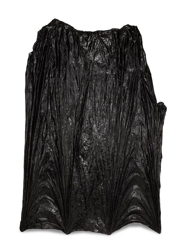 large, rippled black form resembling a wrinkled, windblown tarp