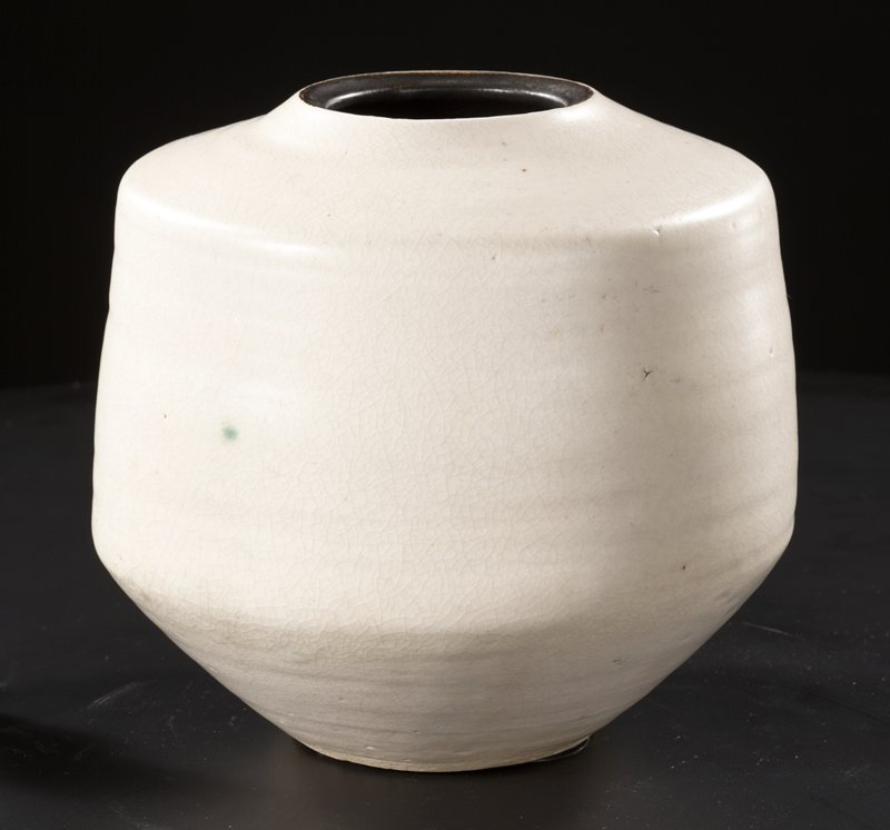 white glazed wheel thrown jar with small, flat opening at top; interior and top lip of jar are glazed black; jar is narrow at bottom and top, tapering into wide, flat sides; white glaze contains specks of other colors including brown, grey, and a prominent green spot