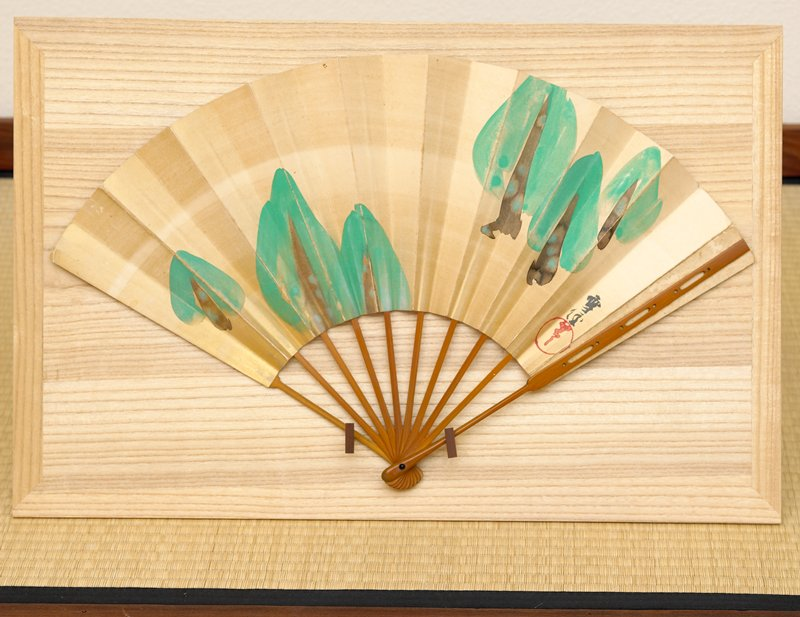 two-sided fan: two groups of three conical, minimalist evergreens; evergreens have dark brown trunks with moss; opposite side: minimalist landscape of mountains in silver and gold pigment