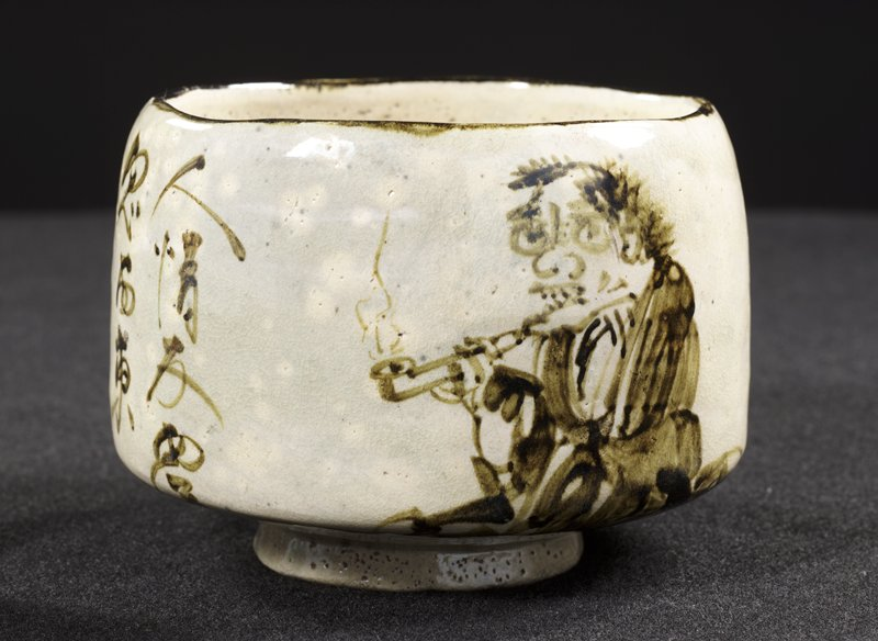 tea bowl with image of a demon smoking a pipe on one side; inscription on other side; white and gray-blue background with opalescent shimmer