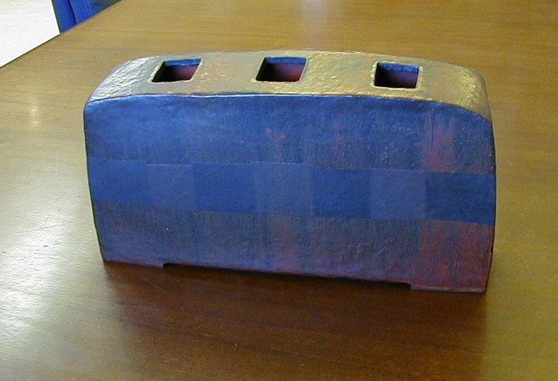 rectangular vessel with rounded top edges; top slopes downward slightly; three square openings in top; dark textured band wrapping around center of form; band has checkered effect on front and back sides; deep red glaze with black overtones; some yellowish detail on top