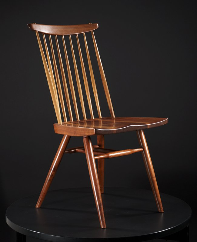 side chair with seat that flares outward towards front, seat carved for body contours; nine narrow spindles on back: lighter wood (hickory?) than rest of chair; top support bar across spindles curves gently outward; top support bar shape is straight across top and curves downward towards center; two small pegs on top bar, one on either side top spindle, with dark wooden inlay; light carved line runs across back of chair seat, through base of spindles; four spindly legs set at outward angles, taper towards ends; spindle shaped crossbar between front and back legs with two parallel spindle shaped bars connecting front and back supports