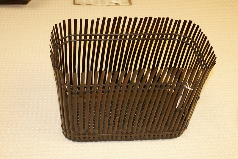 rectangular high-walled basket woven from flat, vertical bamboo strips; uneven at top, resembling windblown reeds; chevron patterned weave at bottom