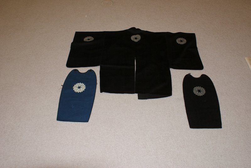 black woolen coat with three white embroidered motifs featuring a circular arrangement of overlapping squares forming 6-pointed star at center; blue woolen breastplate with white motif and black lining; black breastplate with white embroidered motif and blue lining