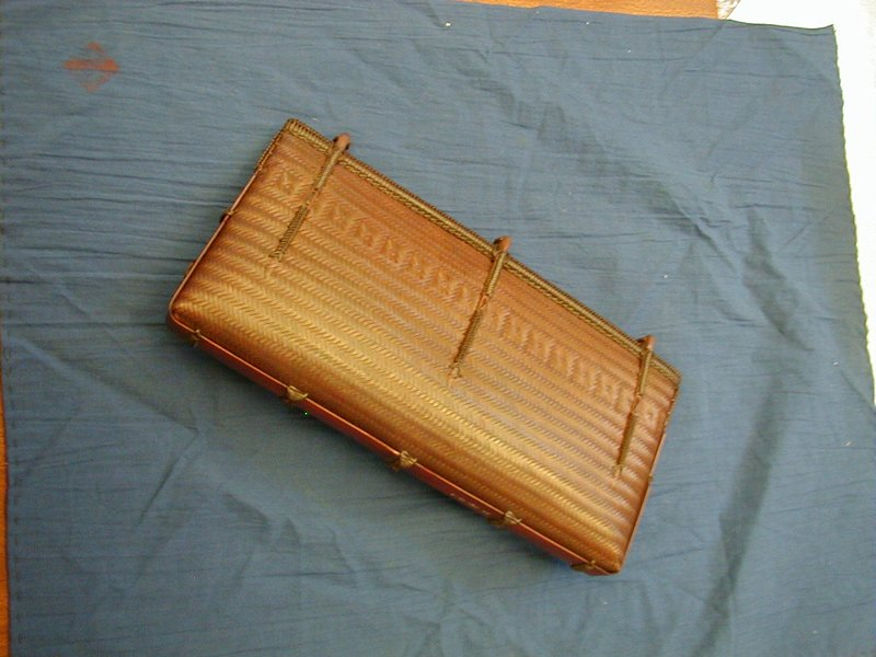 rectangular purse with somewhat rounded, curved bottom; close chevron weave with square pattern near top; three woven vertical strands at top holding woven clasps