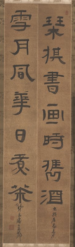 two lines of precisely written characters against brown paper with black flecks