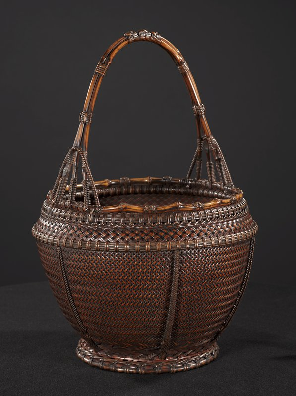 round, closely woven horizontal chevron pattern; widening from base, narrowing slightly at top; bulbous shape; diamond pattern on bottom of interior; top lip of basket decorated with bamboo wound with decorative rosette rattan knots; handle is made of three bent pieces of bamboo secured together with two bands on either side, and three decorative knots at top; anchored by woven arches, forming four prongs on side; inner cylinder is large bamboo stained reddish brown with copper lining