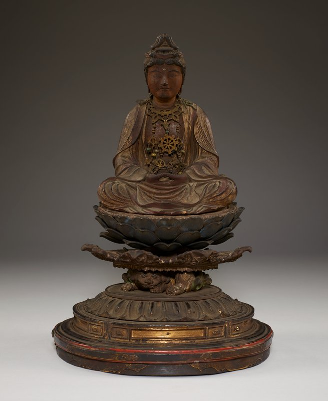 figure seated cross legged with hands upturned in lap, folds of garment flowing over legs; elaborate metal necklace with many low hanging pendants; base is intricately carved with open lotus flower on top of demon creature