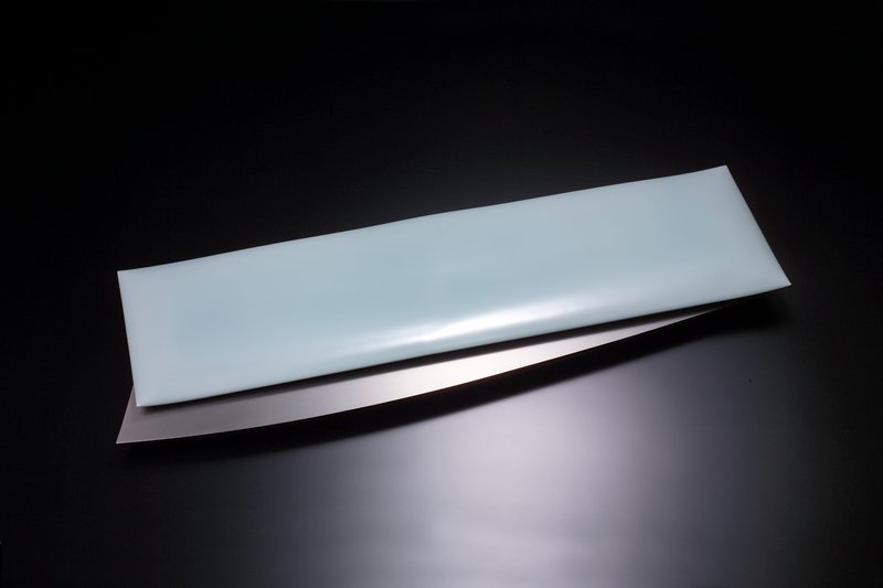 "rectangular porcelain form with pale blue-green glaze; mounted to gently sloping metal ""fin"" at top"