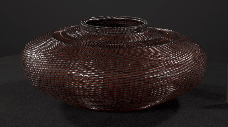 short, squat, round basket with raised lip; closed weave with band of unwove, vertical strands near top