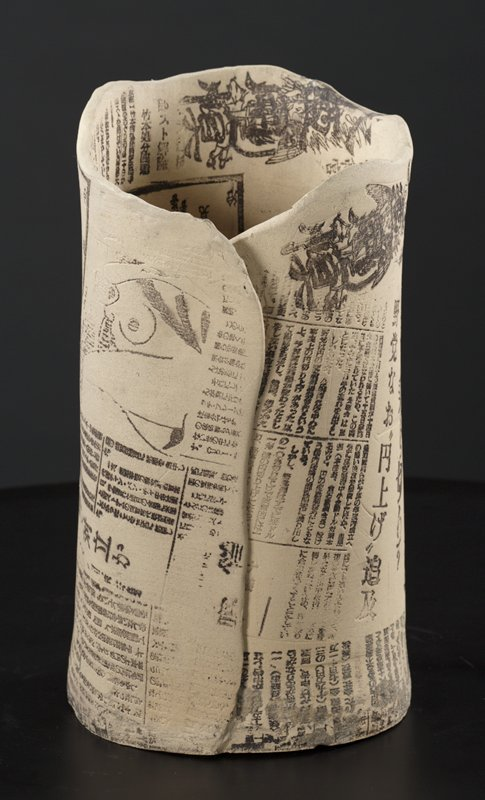 ceramic cylinder with impressed newspaper patterns inside and out; small, black and white humanlike figure with outstretched arms inside